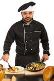 Το αρσενικό αρχιμαγείρων τακτοποιεί τα τρόφιμα στο πιάτο στοκ φωτογραφίες
