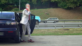 Το αρσενικό βγααλμένο από στο έτη όχημα και μιλά στο τηλέφωνο απόθεμα βίντεο