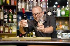 Το αρσενικό δίνει ένα ποτήρι του κόκκινου κρασιού στοκ φωτογραφίες