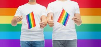 Το αρσενικό ζεύγος με την ομοφυλοφιλική παρουσίαση σημαιών υπερηφάνειας φυλλομετρεί επάνω Στοκ φωτογραφία με δικαίωμα ελεύθερης χρήσης