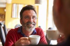 Το αρσενικό ζεύγος πίνει τον καφέ σε ένα εστιατόριο, πέρα από την άποψη ώμων Στοκ Εικόνες