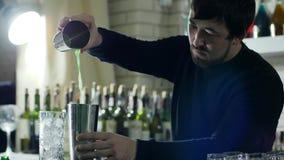 Το αρσενικό μπάρμαν χύνει το φρέσκο χυμό από το φλυτζάνι μετάλλων στο δονητή στο μετρητή φιλμ μικρού μήκους