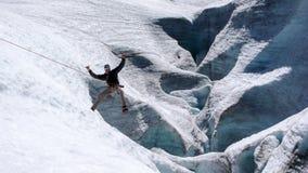 Το αρσενικό παιχνίδι οδηγών βουνών γύρω κατά τη διάρκεια ενός crevasse ξαναξεσηκώνει την άσκηση σε έναν παγετώνα στις Άλπεις στοκ εικόνες