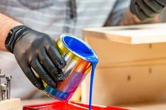 Το αρσενικό παραδίδει τα γάντια που χύνουν το χρώμα στο δίσκο, κινηματογράφηση σε πρώτο πλάνο στοκ φωτογραφίες