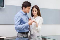 Το αρσενικό παρουσιάζει το δαχτυλίδι αρραβώνων στο κορίτσι του στοκ εικόνα