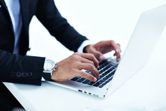 Το αρσενικό πρόσωπο στην πολυτέλεια προσέχει το μήνυμα κειμένου δακτυλογράφησης στον υπολογιστή Στοκ Εικόνα