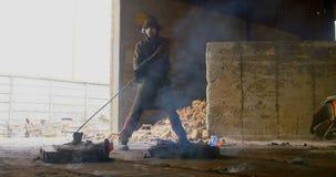 Το αρσενικό τράβηγμα εργαζομένων καυτό το μέταλλο στο εργαστήριο 4k απόθεμα βίντεο