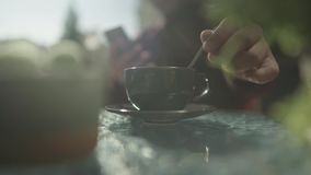 Το αρσενικό χέρι ανακατώνει τον καφέ σε ένα φλυτζάνι απόθεμα βίντεο