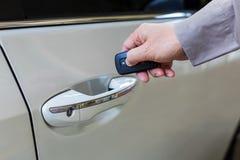 Το αρσενικό χέρι ανοίγει το άσπρο αυτοκίνητο με τη keyless λειτουργία εισόδων στοκ φωτογραφία