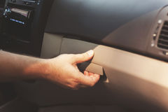 Το αρσενικό χέρι ανοίγει το διαμέρισμα γαντιών στο αυτοκίνητο, αναδρομικός τονισμός Στοκ Φωτογραφία
