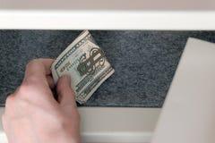 Το αρσενικό χέρι βάζει τα τραπεζογραμμάτια των αμερικανικών δολαρίων σε ένα μεμονωμένο ασφαλές κιβώτιο κατάθεσης Αποθήκευση των τ στοκ εικόνα