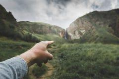 Το αρσενικό χέρι δείχνει την κατεύθυνση της μετακίνησης, πυροβολισμός άποψης Έννοια ταξιδιών περιπέτειας ταξιδιού στοκ φωτογραφία με δικαίωμα ελεύθερης χρήσης