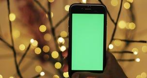Το αρσενικό χέρι είναι εκμετάλλευση Smartphone με την πράσινη οθόνη Φω'τα Blured στο υπόβαθρο απόθεμα βίντεο