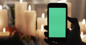Το αρσενικό χέρι είναι εκμετάλλευση Smartphone με την πράσινη οθόνη Αναμμένα κεριά στο υπόβαθρο φιλμ μικρού μήκους