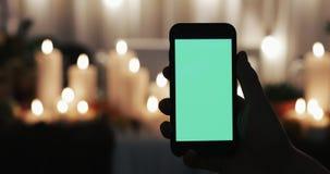 Το αρσενικό χέρι είναι εκμετάλλευση Smartphone με την πράσινη οθόνη Αναμμένα κεριά στο υπόβαθρο απόθεμα βίντεο
