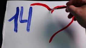 Το αρσενικό χέρι επισύρει την προσοχή τον αριθμό 14 και την κόκκινη καρδιά με τις ηλιόλουστες κίτρινες ακτίνες στη Λευκή Βίβλο απόθεμα βίντεο