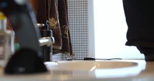 Το αρσενικό χέρι παίρνει μια ηλεκτρική οδοντόβουρτσα στο λουτρό απόθεμα βίντεο