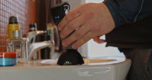 Το αρσενικό χέρι παίρνει την ηλεκτρική ξυριστική μηχανή και την έβαλε  απόθεμα βίντεο