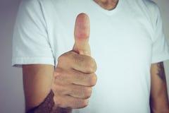 Το αρσενικό χέρι που παρουσιάζει αντίχειρες υπογράφει επάνω Στοκ Εικόνες