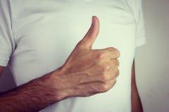 Το αρσενικό χέρι που παρουσιάζει αντίχειρες υπογράφει επάνω Στοκ εικόνες με δικαίωμα ελεύθερης χρήσης
