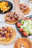 Το αρσενικό χέρι που τρώει τη φυτική σαλάτα και το της Γαλικίας ύφος μαγείρεψε το χταπόδι με το ελαιόλαδο πάπρικας και gallega pu Στοκ φωτογραφία με δικαίωμα ελεύθερης χρήσης