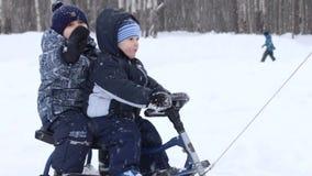 Το αρσενικό χέρι σέρνει δύο ευτυχή μικρά παιδιά στο έλκηθρο κοντά σε άλλο αγόρι κατά τη διάρκεια των χιονοπτώσεων στο πάρκο φιλμ μικρού μήκους