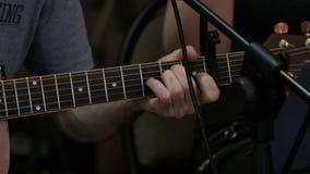 Το αρσενικό χέρι στερεώνει τις σειρές σε μια ακουστική κιθάρα για την υγιή εξαγωγή Σόλο κινηματογράφηση σε πρώτο πλάνο μουσικών ή φιλμ μικρού μήκους