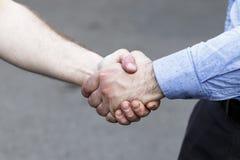 Το αρσενικό χέρι συμπιέζει το άλλο χέρι r r στοκ εικόνα