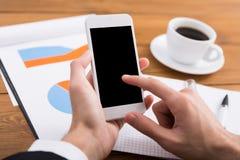 Το αρσενικό χρησιμοποιώντας τηλέφωνο στον εργασιακό χώρο, κλείνει επάνω Στοκ φωτογραφίες με δικαίωμα ελεύθερης χρήσης