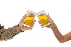 Το αρσενικό δύο παραδίδει τα πουκάμισα κρατά τα έξυπνα τηλέφωνα με την μπύρα στο άσπρο κλίμα Στοκ Εικόνα