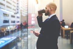 Το αρσενικό CEO με το τηλέφωνο κυττάρων υπό εξέταση σκέφτεται για το σχέδιο εργασίας Στοκ φωτογραφίες με δικαίωμα ελεύθερης χρήσης