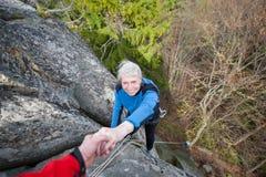 Το αρσενικό rockclimber βοηθά ένα θηλυκό ορειβατών Στοκ Εικόνες