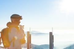 Το αρσενικό snowboarder που παίρνει έτοιμο για οδηγά προς τα κάτω από την κορυφή ενός βουνού Στοκ Εικόνες