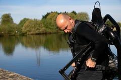 Το αρσενικό thrillseeker, αθλητικός εραστής νερού, αθλητής που δένεται στο αεριωθούμενο LEV, μετεωρισμός προετοιμάζεται να πετάξε Στοκ Εικόνα