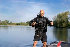 Το αρσενικό thrillseeker, αθλητικός εραστής νερού, αθλητής που δένεται στο αεριωθούμενο LEV, μετεωρισμός προετοιμάζεται να πετάξε Στοκ Φωτογραφία