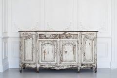 Το αρχαίο λευκό γραφείο κομό με το χρώμα ξεφλούδισε μακριά στα στοιχεία roccoco σχημάτων στόκων bas-ανακούφισης σχεδίου τοίχων πο Στοκ Εικόνες