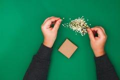 Το αρχικό σχέδιο ενός δώρου Χριστουγέννων του εγγράφου τεχνών, σκωτσέζικος και του κομφετί των χρυσών αστεριών σε ένα πράσινο υπό στοκ εικόνα