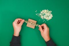 Το αρχικό σχέδιο ενός δώρου Χριστουγέννων του εγγράφου τεχνών, σκωτσέζικος και του κομφετί των χρυσών αστεριών σε ένα πράσινο υπό στοκ φωτογραφία