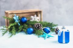 Το ασημένιο και μπλε δώρο παιχνιδιών, χύσιμο παιχνιδιών Χριστουγέννων από το ξύλινο κιβώτιο με οι κλάδοι δέντρων Στοκ εικόνες με δικαίωμα ελεύθερης χρήσης