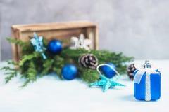 Το ασημένιο και μπλε δώρο παιχνιδιών, χύσιμο παιχνιδιών Χριστουγέννων από το ξύλινο κιβώτιο με οι κλάδοι δέντρων Στοκ Εικόνες