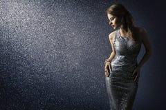 Το ασημένιο φόρεμα, διαμορφώνει την πρότυπη τοποθέτηση στη λαμπιρίζοντας προκλητική εσθήτα στοκ εικόνα