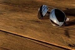 Το ασημένιο χρώμα γυαλιών ηλίου είναι στον ξύλινο πίνακα Στοκ Φωτογραφίες