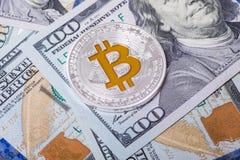 Το ασημένιο bitcoin βρίσκεται στους λογαριασμούς 100 δολαρίων Bitcoin στο υπόβαθρο δολαρίων Στοκ Φωτογραφία