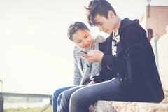 Το ασιατικά αγόρι και το κορίτσι εφήβων κοιτάζουν στο smartphone, επικοινωνούν, έχουν fu Στοκ φωτογραφία με δικαίωμα ελεύθερης χρήσης