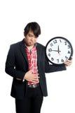 Το ασιατικό άτομο έχει την κακή συνήθεια κατανάλωσης να πάρει το στομαχόπονο με το ρολόι στοκ εικόνα