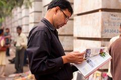 Το ασιατικό άτομο κτυπά μέσω του περιοδικού στην οδό στοκ φωτογραφίες