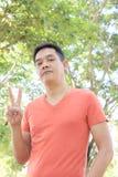 Το ασιατικό άτομο παρουσιάζει το δάχτυλο δύο και φυσικό υπόβαθρο Στοκ Εικόνα