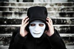 Το ασιατικό άτομο στη μαύρη κουκούλα και η λευκιά μάσκα με ταραγμένο πιέζουν Στοκ φωτογραφία με δικαίωμα ελεύθερης χρήσης
