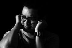 Το ασιατικό άτομο στο σκοτάδι καλύπτει τα αυτιά του Στοκ εικόνες με δικαίωμα ελεύθερης χρήσης