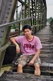 Το ασιατικό άτομο της Ταϊλάνδης κάθεται στη γέφυρα Στοκ φωτογραφία με δικαίωμα ελεύθερης χρήσης